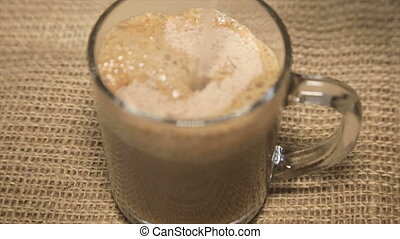 Coffee drink filled with boiling water in a glass cup on sacking