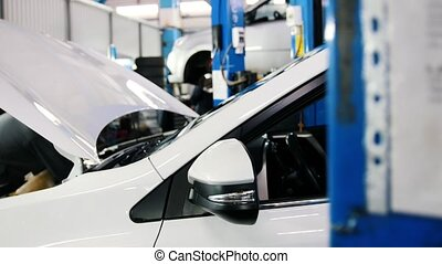 Open the hood of the car - the engine, the battery, the injector - mechanic working in the automotive service, slider