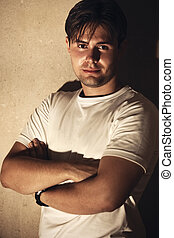 Young man on wall background. Night lighting.
