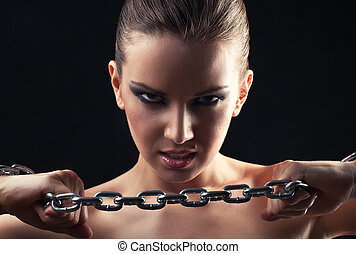 Young fashion woman breaking metallic chain.