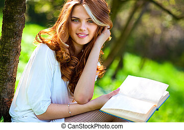 Young woman reading book in summer park