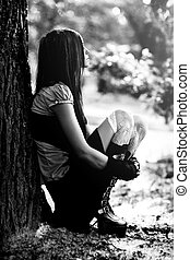 Young thoughtful woman sitting in park Black and white
