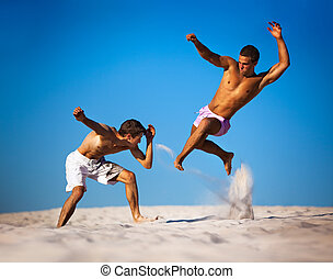 Two young men sport fighting on beach.