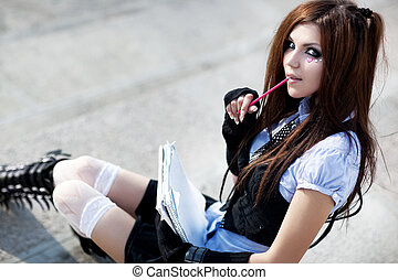 Young schoolgirl sitting on stairs.