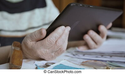 Hands of an old woman who works on tablet - Old woman and...