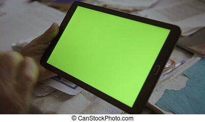 A blank tablet PC in landscape orientation with a green...