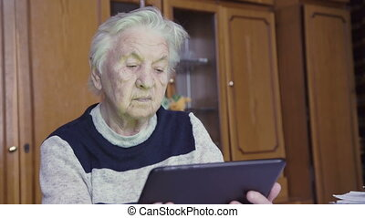 Old woman and electronic tablet. 4k