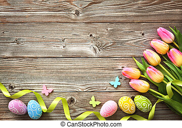 Easter background with colorful eggs and spring tulips -...