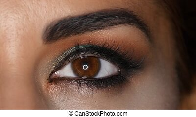 Girl with make up looks fascinating look and blinks. Close up