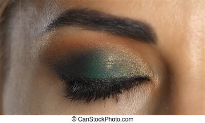 Girl with make up opens eyes and looks before. Close up -...