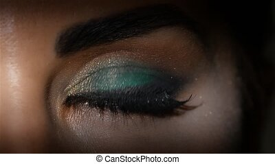 Girl with make up looks languid eyes and blinks. Close up