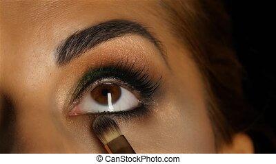 Girl with make up looking up, visagiste brush adjusts her...