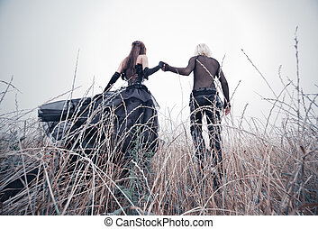 Young goth couple walking on field. Bright white colors.