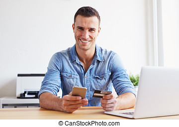 Man sitting in office and pays by credit card