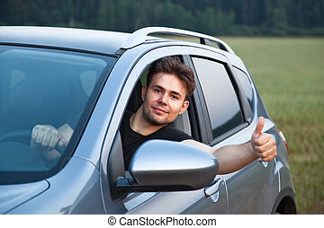 Young man looking out of car and showing success handsign