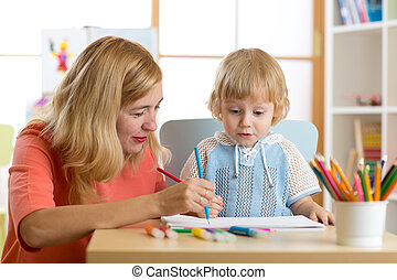 Mother playing with her child son, drawing together