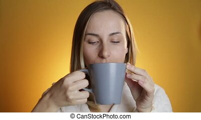 woman drinking tea from a mug on a yellow background