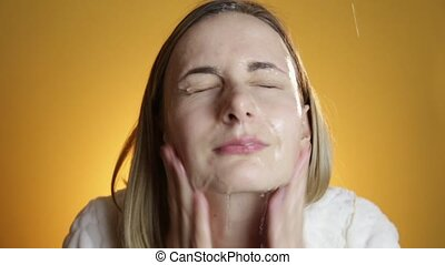 Blonde woman splashing her face against a on a yellow...