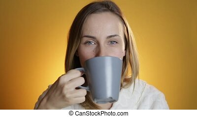 Beautiful young woman dreaming with cup of hot coffee on a...