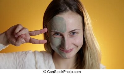 Skin care. Woman applying with brush clay mud mask to her...