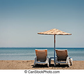 Two old beach chairs and sun umbrella on the background of...