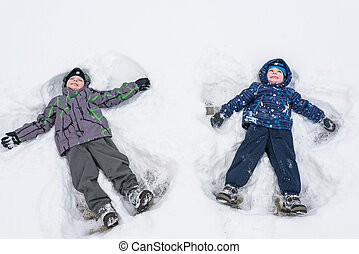 Two little siblings kid boys in colorful winter clothes making snow angel, laying down on . Active outdoors leisure with children in . Happy brothers