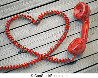 Phone reciever and cord as heart on white wooden background....