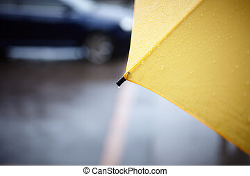 rainy walk with yellow umbrella, selective focus on part...