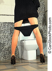 woman stays near toilet bowl - part of the woman who stays...