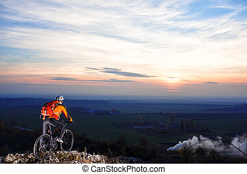 Cyclist with backpack on the top of a hill