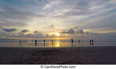 Exciting time-lapse of beautiful sunset over the ocean with blue sky and golden water surface. Silhouettes of people walking here and there with increasing speed on Balinese beach.