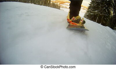 Snowboard board close-up. Legs snowboarder. Speed.