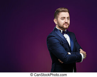 Handsome man in tuxedo and bow tie looking at camera. Fashionable, festive clothing. Space for text