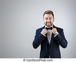 Handsome man in tuxedo and bow tie looking at camera. Fashionable, festive clothing. emcee on grey background