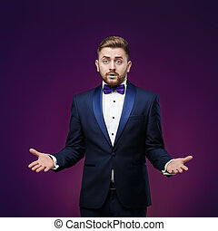 Handsome man in tuxedo and bow tie is surprised, throws his hands. compere in fashionable, festive clothing