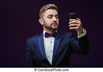 handsome man in tuxedo and bow tie makes selfie against dark background. Fashionable, festive clothing
