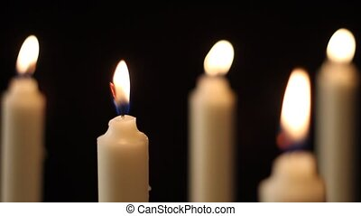 Candles - Multiple candles slowly flicker with a black...