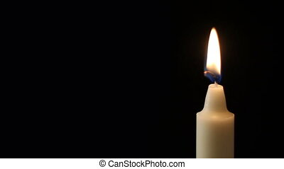 Candle - A single candle slowly flicker with a black...