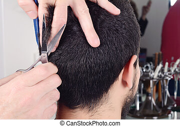 Young man having a haircut with scissors.