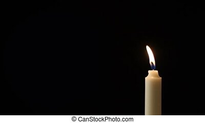 Candle - A single candle slowly flickers - with a black...