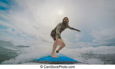 Young man rides a surfboard, catch a small ocean wave, and...
