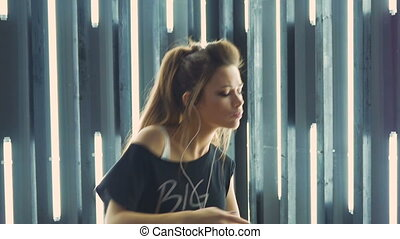 Beautiful young woman dancing in a nightclub, listening to music through headphones. Slow motion.