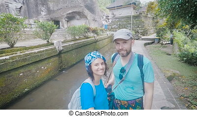 Young couple relaxing on an exotic island and shoots video selfie with the help of sticks. The guy and the girl show the old buildings and the beautiful nature that surrounds them.