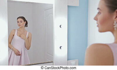 Portrait of woman with make-up looking at her reflection in mirror, fixing hair