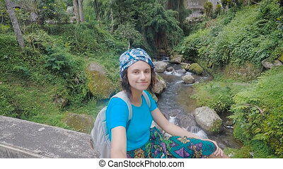 Female traveler sitting on the edge of bridge holding...