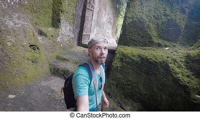 Young man walks through the incredibly beautiful island and surprise considers attractions and beautiful scenery. Tourist shoots video in memory of the journey using the selfie stick.