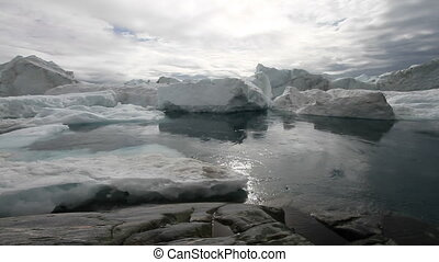 Water and Icebergs - Calm moving water in front of some...