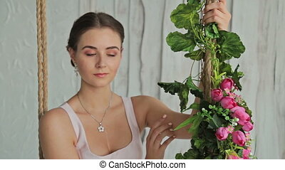 3 shots. Woman with make-up and hairstyle on a swing decorated with flowers.
