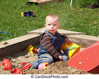Girl in sand-pit - Little girl sitting inside the sand-pit