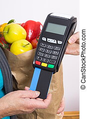 Hand of senior woman using payment terminal with credit card, cashless paying for shopping